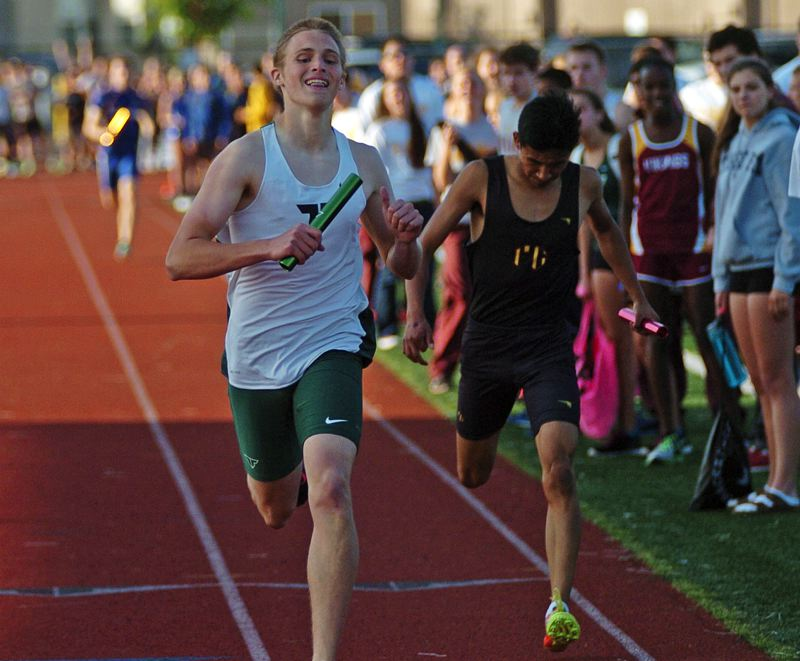 by: DAN BROOD - HAPPY WINNER -- Tigard sophomore Tyler Rosette (left) smiles as he crosses the finish line in the 4 x 400 relay.