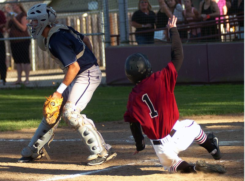 by: DAN BROOD - SLIDING IN -- Sherwood senior Beau Curtiss slides safely home while Wilsonville catcher Cooper  Whitaker awaits the throw in Monday's game. The Bowmen got a 7-2 win.