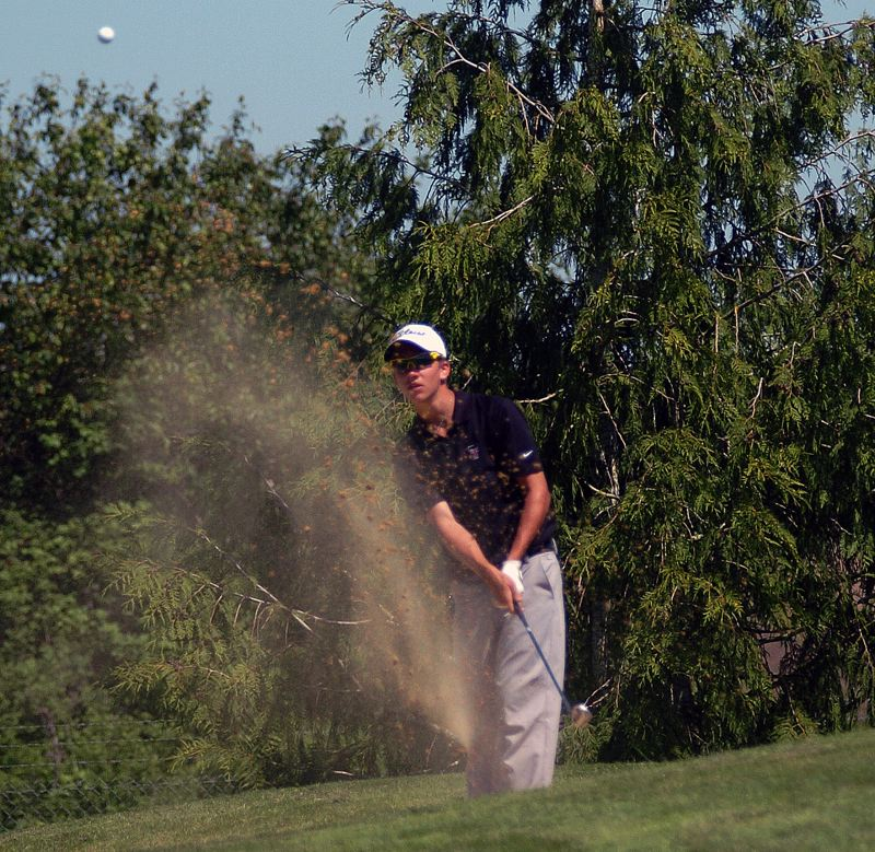 by: DAN BROOD - BUNKER TO BIRDIE -- Tualatin's CJ Luikart hits this shot out of the bunker on hole No. 14. The ball ended up going into the cup for a birdie.