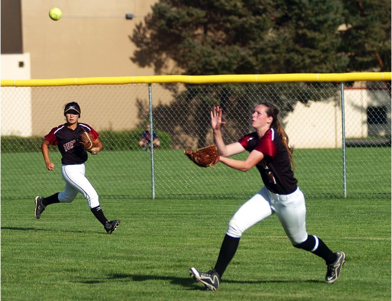 by: DAN BROOD - MAKING THE PLAY -- Tualatin sophomore right fielder Hannah Self (right), with center fielder Caitlyn Sung to her right, gets under a fly ball during the Wolves' win at Glencoe on Tuesday.