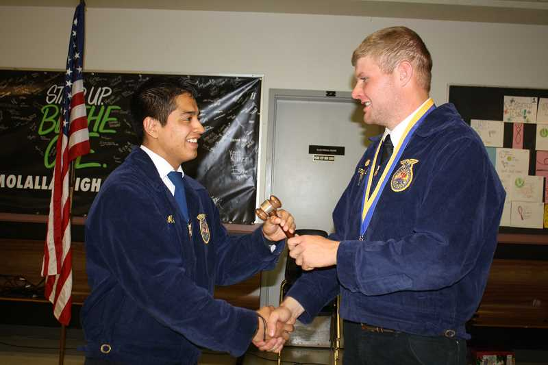 by: PEGGY SAVAGE - Molalla FFA 2013-14 President Kenny Schriever, right, hands over the gavel to Luis Mendoza, the club's new president for the coming year.