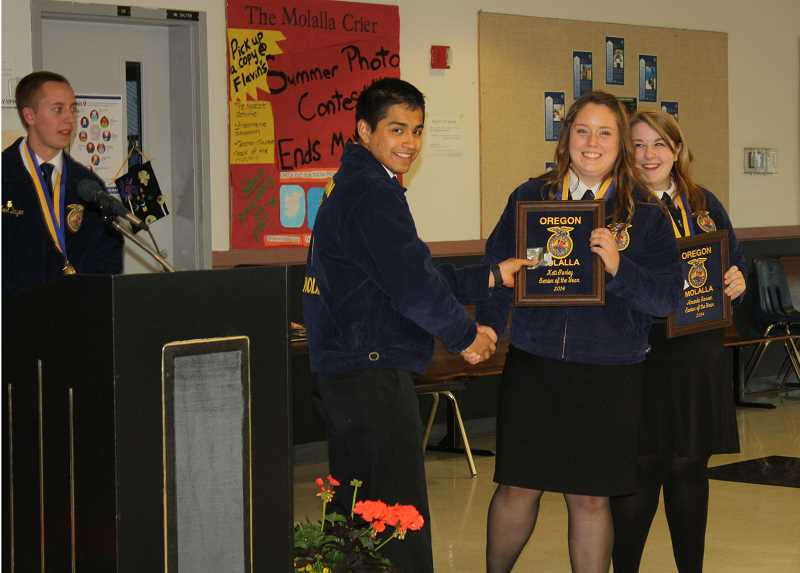 by: PEGGY SAVAGE - Carl Beyer, at podium, and Luis Mendoza congratulate Kati Gurley, left, and Amanda Serven, named 2014 Seniors of the Year.