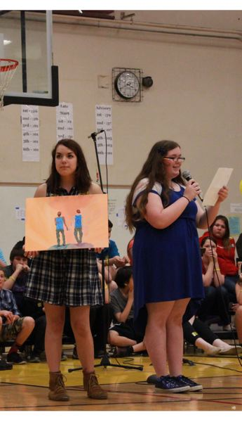 by: PHOTO BY: COREY BUCHANAN - Alder Creek Middle School student Beatrice Degraw reads an essay for classmate Audra Erickson, who won a prize for the artwork she's holding.