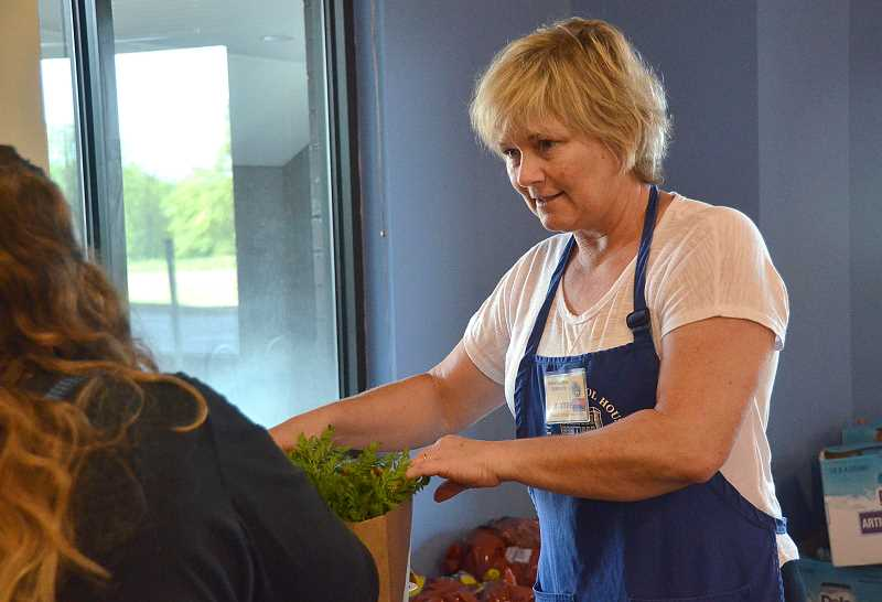 by: STAFF PHOTOS: VERN UYETAKE - Lake Oswego resident Joanne Clayton helps a client of the Tualatin School House Pantry pack a bag of food.
