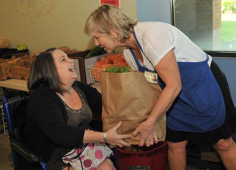 Connie Dover of Tualatin receives a bag of groceries and a smile from Clayton.