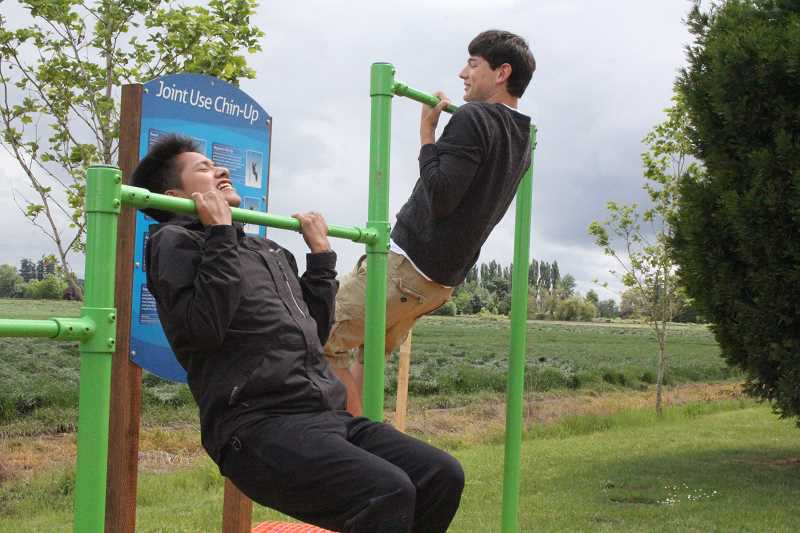 by: LINDSAY KEEFER - Cesar Ramos (on left) and Joey Mack demonstrate how to use one of the new exercise stations at Centennial Park Sunday.