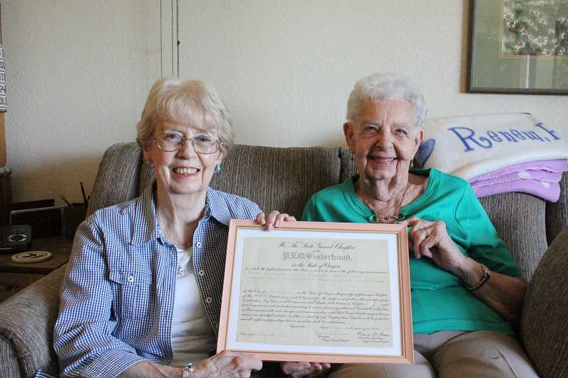 by: LINDSAY KEEFER - Roberta Campbell (left) and Carol Eaden, 50-year members of PEO Chapter J, hold up the club's charter from May 20, 1914.
