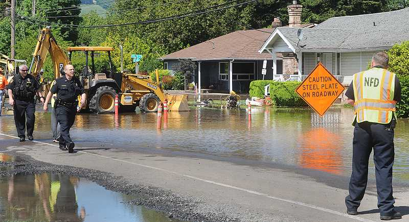 by: AL HERRIGES - Fire, police and ODOT crews survey a water main break on North College Street on Tuesday afternoon