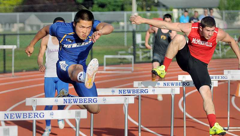 by: SETH GORDON - Total focus - Newberg senior Andy Tautfest duels with McMinnville's Tanner Scanlon en route to a second-place finish in the 300-meter hurdles Friday at the Pacific Conference track and field championships at Newberg High School. Tautfest also qualified for the state meet by placing second in the 110 hurdles, as the Tigers won the boys event with 138.5 points.
