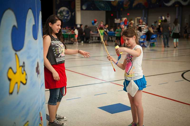 by: TIMES PHOTO: ADAM WICKHAM - Jadyn Smith, 9, examines the jump rope she won in the fishing game.