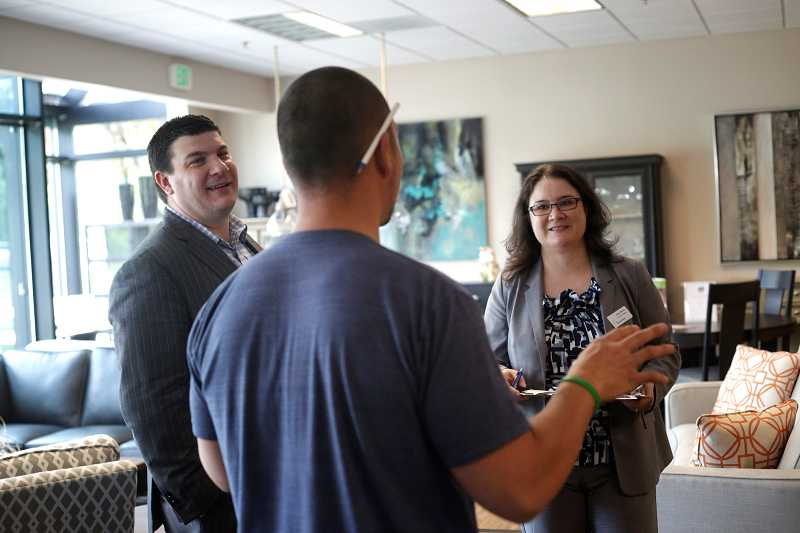by: TIMES PHOTO: JONATHAN HOUSE - Tony Cunningham and Alma Flores chat with business owner Brendan Yee of Belle Furniture during the Beaverton Area Chamber of Commerce's Business Walk to gauge business owners' feelings on the economy and the local business climate.