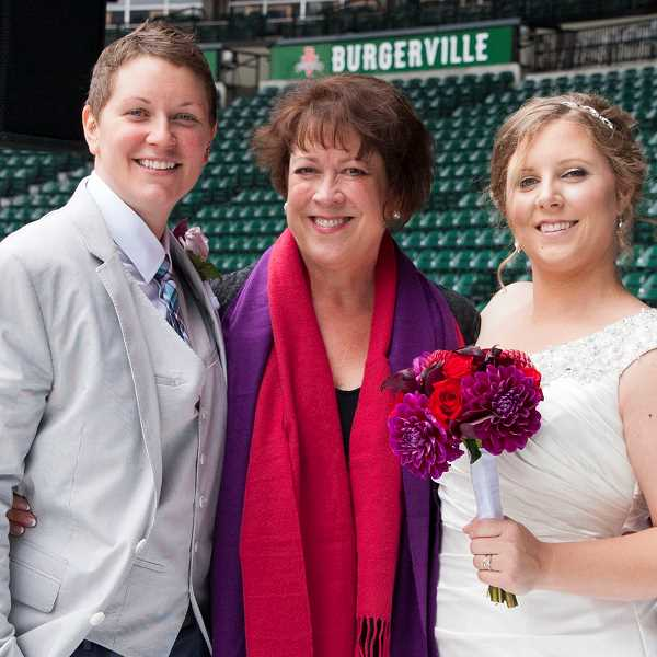 by: SUBMITTED PHOTO - Melissa Coe, an officiant who owns Melissa Coe Ceremonies in Lake Oswego, stands in Jeld-Wen Field in Portland with a pair of clients who tied the knot: from left, Sarah and Kate (last names withheld for privacy).
