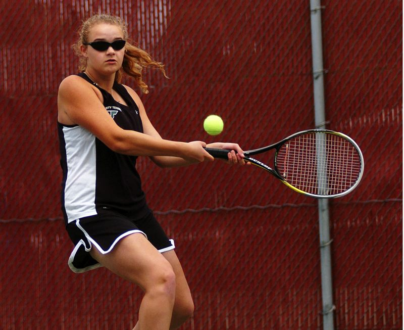 by: DAN BROOD - BIG BACKHAND -- Tigard High School senior Courtney Roshak hits a shot during the girls singles title match Saturday during play at the Pacific Conference district tournament.