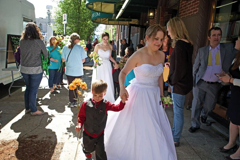 by: TRIBUNE PHOTO: JAIME VALDEZ - Anna Rigles and her wife, Sarah, hold hands with their 4-year-old twins, Tristan and Liam,  after getting married Monday afternoon at the Melody Ballroom. The Rigles bought their wedding dresses early in the day and had them altered by 2 p.m. in time to get married.