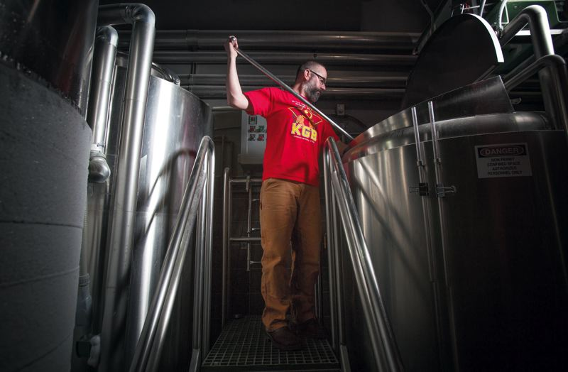 by: TRIBUNE PHOTO: JONATHAN HOUSE - Ben Dobler of Widmer Brothers stirs a tank at the brewerys pilot location in the Moda Center.