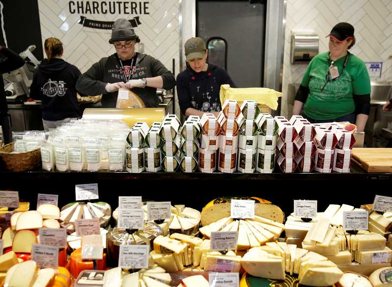 by: TIMES PHOTO: JONATHAN HOUSE - Whole Foods employees prepare the cheese department at the stores new location in Tigard.