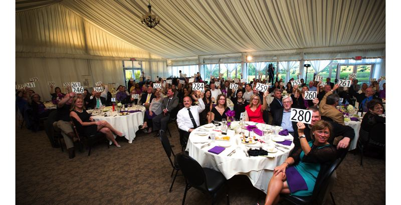 by: PHOTO BY: JULIANA PATRICK - Attendees at Clackamas Womens Service Heroes of Hope Gala hold up their bid numbers May 17.