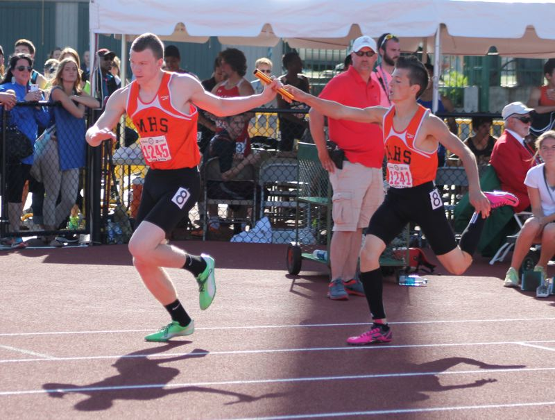 by: JIM BESEDA/MOLALLA PIONEER - Molalla's Payton Dobbs takes the baton from Scott Chance for the second leg of the 4x400-meter relay during Saturday's OSAA Class 4A track and field championships at Hayward Field in Eugene. The Indians finished eighth in a season-best time of 3:30.07.