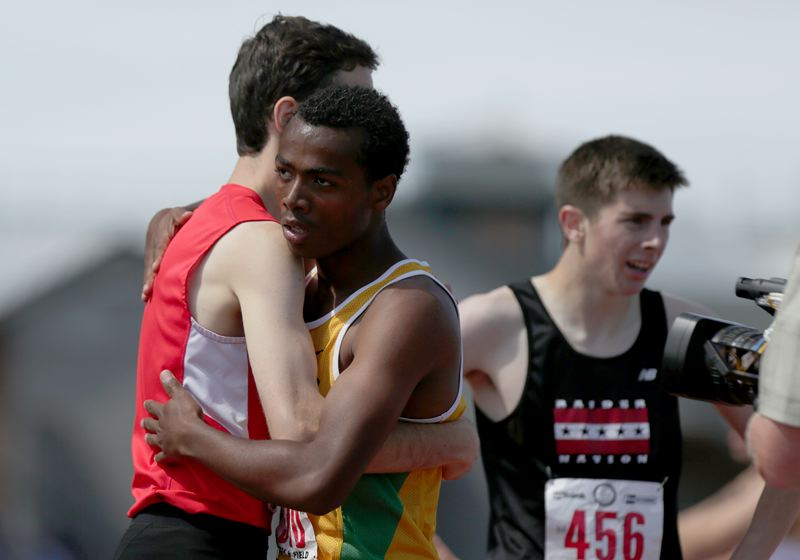 by: TRIBUNE PHOTO: JONATHAN HOUSE - Cleveland's Roba Sultessa gives a tired hug after setting a new State Track meet record in the 5A Boy's 800 meter run.
