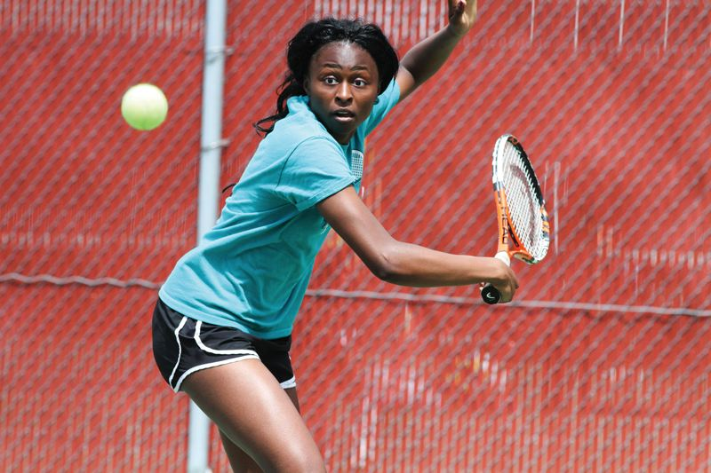 by: HILLSBORO TRIBUNE PHOTO: AMANDA MILES - Century junior Eka Essien tracks a shot during the Pacific Conference tennis tournament last week. Essien won her third straight singles title.