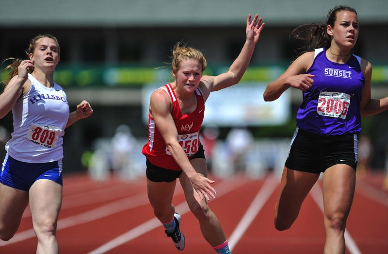 by: JOHN LARIVIERE - Oregon City senior Becca Houk (center) lunges for the finish line to beat Hillsboro junior Anna Dean and Sunset senior Taylor Coon by a nose for a state championship in the 100-meter dash.