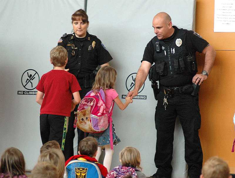 by: ISABEL GAUTSCHI - Sandy/Estacada Police Chief Kim Yamashita and Officer Bill Wetherbee shake hands with citizenship award recipients at Clackamas River Elementary on Monday, May 19.