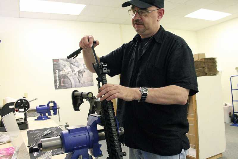 by: TYLER FRANCKE | WOODBURN INDEPENDENT - Craig Andersen, president and co-owner of TacTek Arms in Woodburn, cleans the barrel of a custom-built AR-15 rifle.