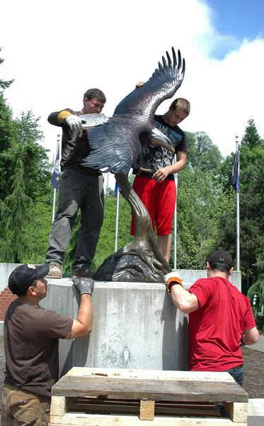 by: ESTACADA NEWS PHOTO: BEVERLY CORBELL - Shane Stofner, top left, and Roy Swan Jr. help position the new bronze eagle at Estacada Veterans Memorial with the help of Mario Pinto, bottom left, and Roy Swan Sr.