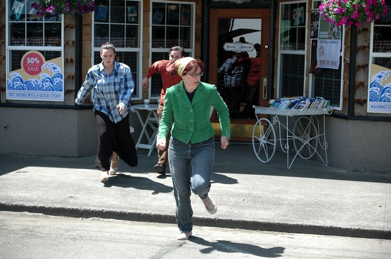 by: ESTACADA NEWS PHOTO: BEVERLY CORBELL - Jessica Fisher, left, and Angie Melfa, Estacada residents working as extras on The Librarians for TNT, race away from Barbaras Flowers and Coffee in one scene.