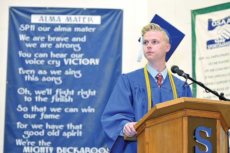 by: GARY ALLEN - SPHS - Master of Ceremonies Austin Burleson presides over St. Paul High School's commencement ceremony Saturday before a crowd that packed the school's gymnasium.