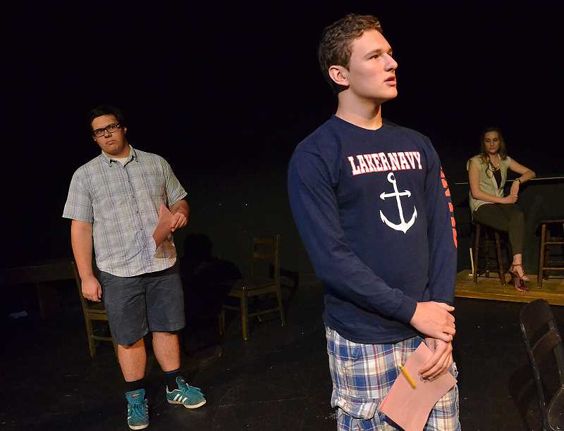 by: REVIEW PHOTO: VERN UYETAKE - Tom (played by sophomore Noah VanderVeer-Harris), center, shares his war memories  while his younger self, played by junior John Hanifin looks on. Cast member Ellie Ulrich sits in the background.