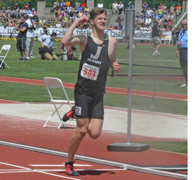 by: TIMES PHOTO: MATT SINGLEDECKER - Jesuit senior long distance runner Michael Godbout pumps his fist in celebration as he crosses the finish line of his 1,500 win at the 6A state championship meet on Saturday.