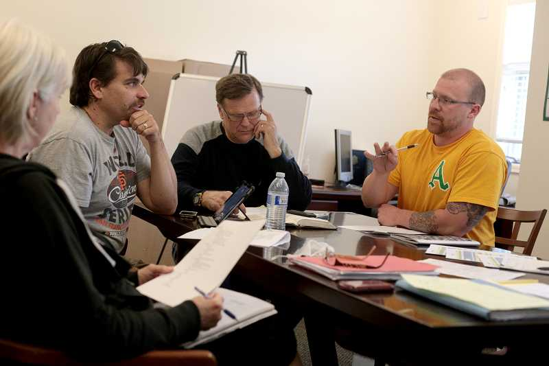 by: TIMES PHOTO: JONATHAN HOUSE - From left, Beth Werner, Tom Houser, John Werner, and Paul Allen Riggs discuss logisitics of setting up Portland Community Church's new building at 7100 S.W. Scholls Ferry Road.