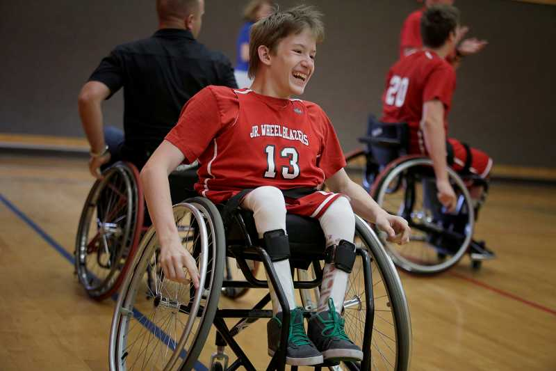 by: TIMES PHOTO: JONATHAN HOUSE - Junior Wheel Blazers member Josiah Schuremyer smiles after making a shot during an exhibition at Woodward Elementary School.