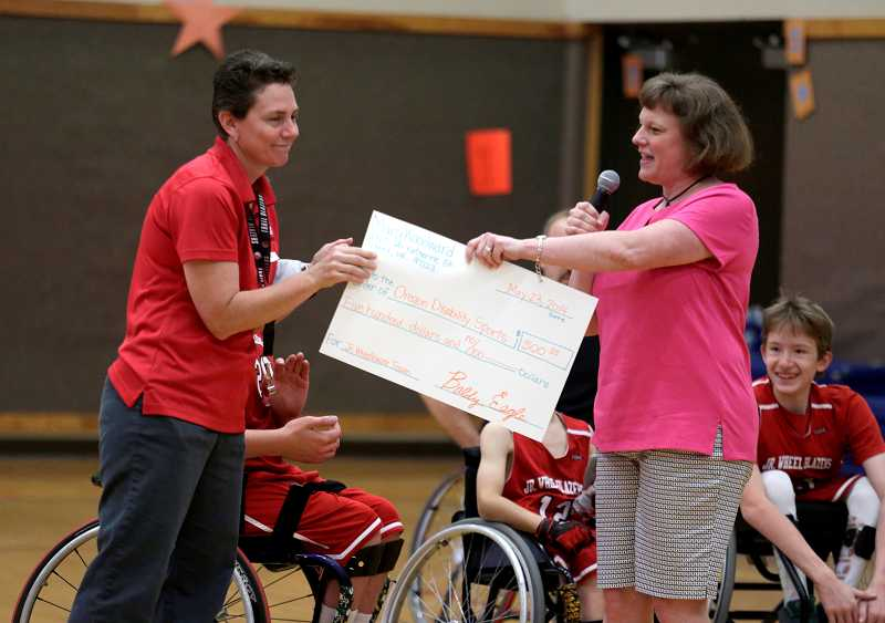 by: TIMES PHOTO: JONATHAN HOUSE - Junior Wheel Blazers coach Laura Ridler accepts a check for $500 from the kids at Woodward Elementary for her team.