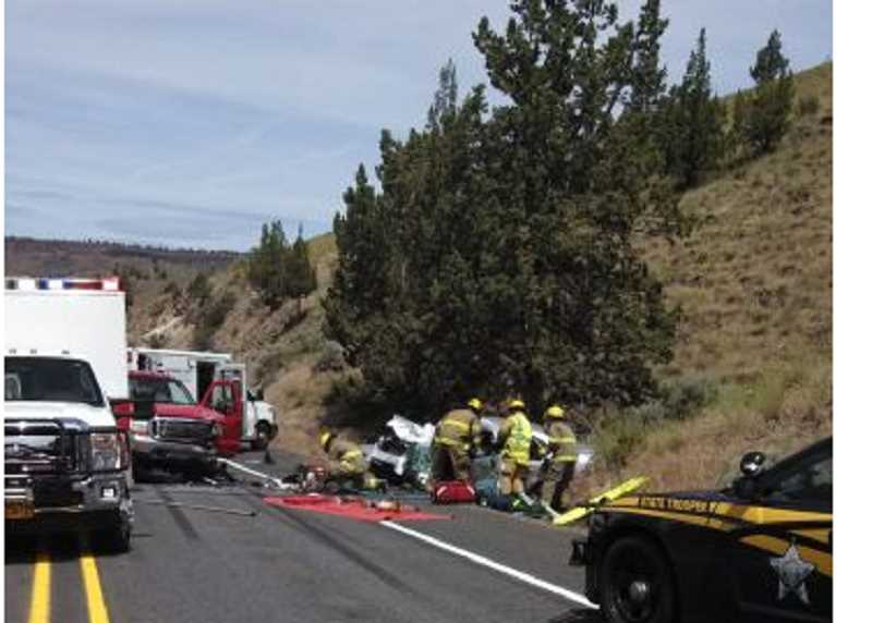 by: SUBMITTED PHOTO - A rescue crew attends to victims of a crash on U.S. Highway 26 west of Madras on May 25.