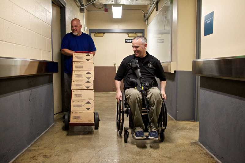 by: TIMES PHOTO: JAIME VALDEZ - Brett Williamson follows Portland Police Officer Paul Meyer to his vehicle with boxes of ammunition at the Central Precinct in downtown Portland. Williamson is a Fire & Police Disability Retirement liaison with the city of Portland.
