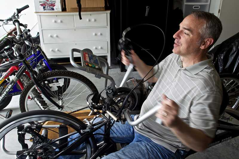 by: TIMES PHOTO: JAIME VALDEZ - Portland Police Officer Paul Meyer uses a Freedom Ryder bike made in Tualatin as a form of exercise in his home in Tualatin.