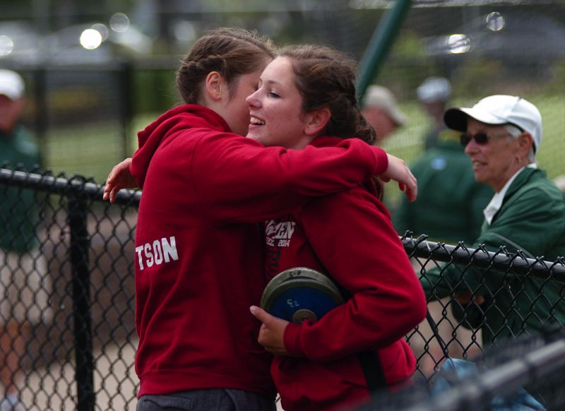 by: DAN BROOD - SISTER ACT -- Sherwood senior Elyse Cuthbertson (right) gets a hug from her younger sister, Payge, after winning the state title in the discus event.