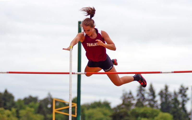 by: DAN BROOD - HIGH IN THE SKY -- Tualatin senior Laura Taylor clears the bar during the Class 6A girls pole vault competition.