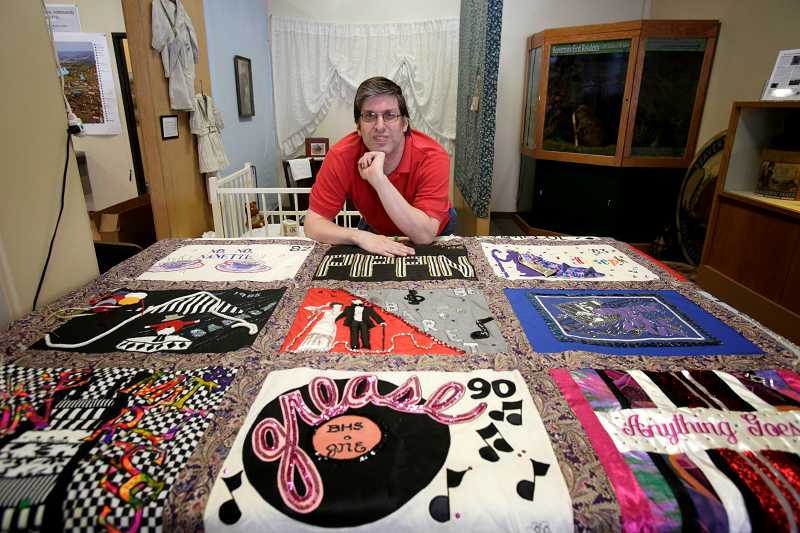 by: TIMES PHOTO: JONATHAN HOUSE - Michael Shafer-Montgomery, chairman of the James N. Erickson Legacy Project, displays the quilt featuring all of Erickson's shows from 1971 to 1995. The quilt was made by mothers and cast members.