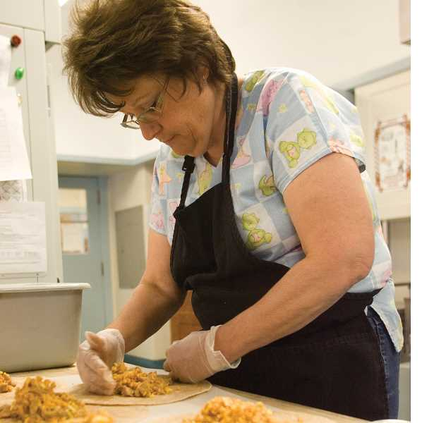 by: KEVIN SPERL - Charlene Osborne wraps burritos for lunch in the district production kitchen. Osborne will be part of the team producing food for the summer meals program.