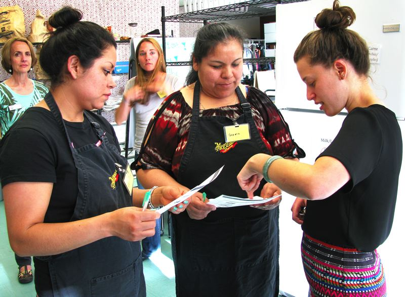 by: OUTLOOK PHOTO: LISA K. ANDERSON - Maria Castro Guzman and Gloria Castro Guadian chat with Melanie Epstein, a Reynolds SUN AmeriCorps member, about the recipes they created with Reynolds Middle School food pantry items.