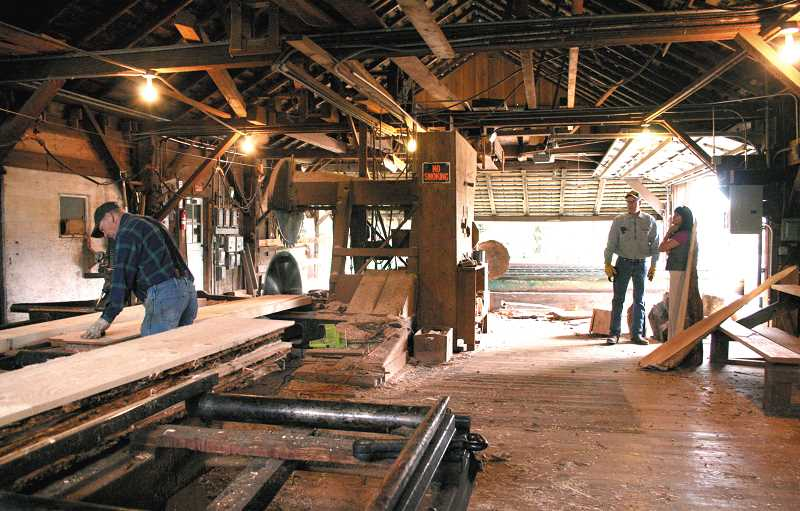by: RACHEL ALDRICH - Lowell Boyce, left, runs a saw at Yoder Mill last week. David Yoder, standing with Bernadette Yoder, right, runs the mill started by his ancestor, Jonathan S. Yoder, in 1889 and handed down through the Yoder family for generations.