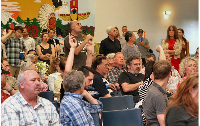 by: DAVID F. ASHTON - Many hands go up, as attendees make comments and pose questions at the Street User Fee meeting held on May 1st in Woodstock.