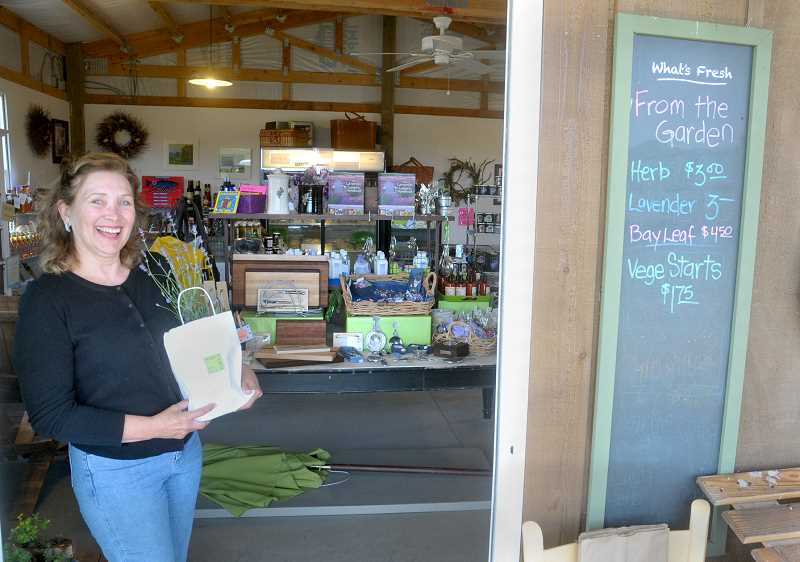 by: GARY ALLEN - Displaying her wares - Jan Ellings and Phil Cleys own the Chehalem Flats Farm Market near the intersection of North Valley and Dopp roads.