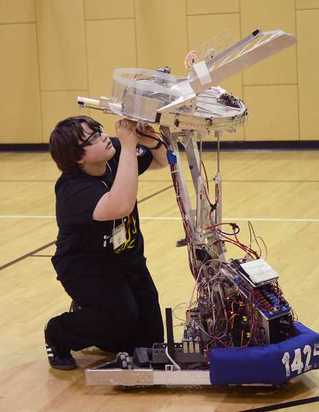 by: TIDINGS PHOTO: VERN UYETAKE - Team member Adrian Hardt makes an adjustment to FIRST Team 1425s robot.