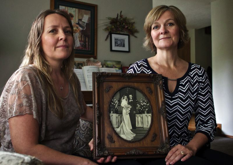 by: TRIBUNE PHOTO: JAIME VALDEZ - Karen Jackson of Forest Grove and her sister, Lorretta Krautscheid, hold a wedding photo of their parents, Ethel and Edwin Duyck. They know for certain that their father's side of the family carries the BRCA gene.