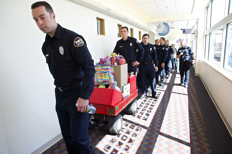 by: TIMES PHOTO: JAIME VALDEZ - Thirteen Tualatin Valley Fire & Rescue firefighter recruits deliver a collection of toys Friday to Oregon Health and Science University's Doernbecher Children's Hospital.