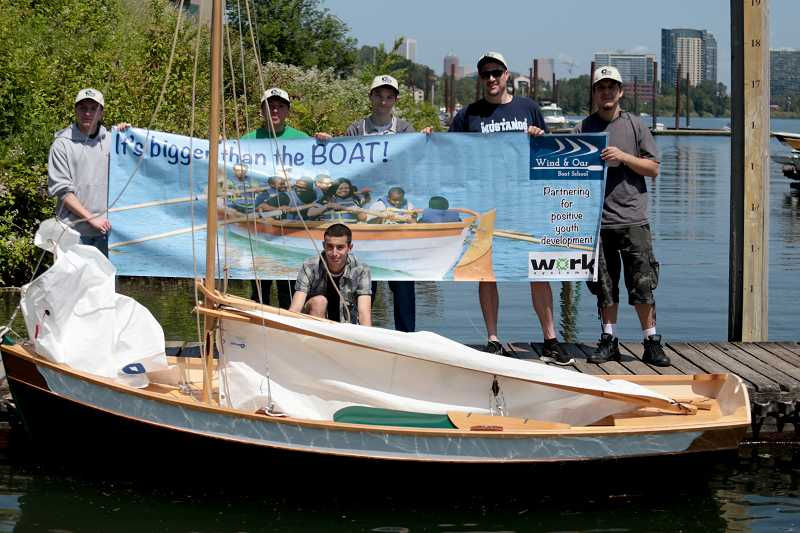 by: TIMES PHOTO: JONATHAN HOUSE - The students of Merlo Station High School in Beaverton and their mentor Matt Laughner pose with the boat they built prior to its maiden voyage on the Willamette River.
